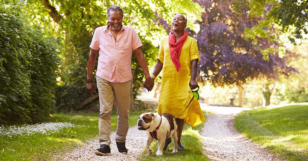 senior couple walking dog outside