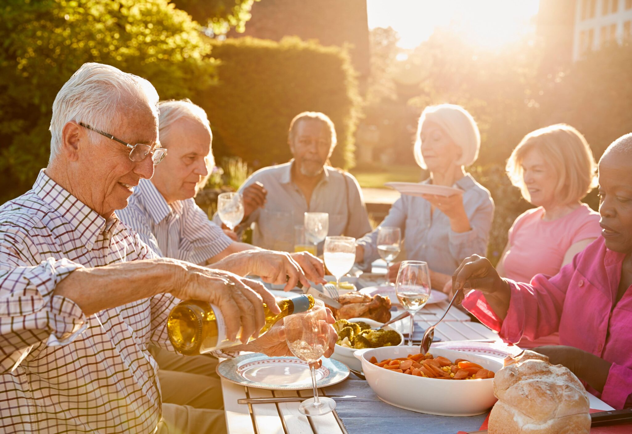 A group of seniors enjoy social wellness with a dinner outside together.