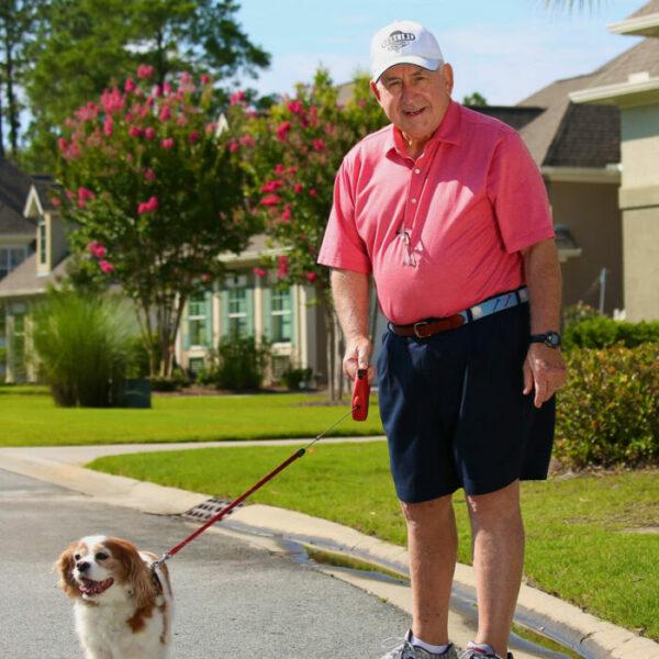 A senior man walks his dog in the Marshes of Skidaway Island senior neighborhood