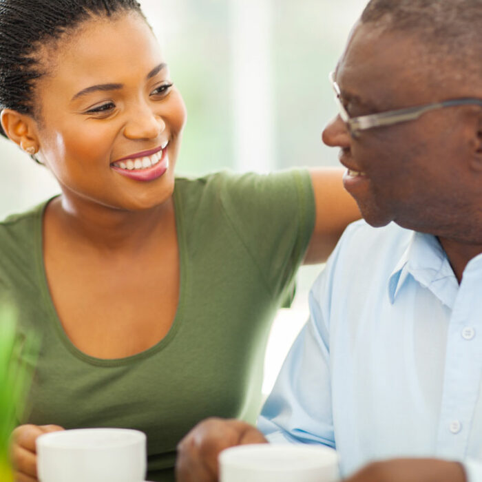 A woman meets with her elderly father over coffee