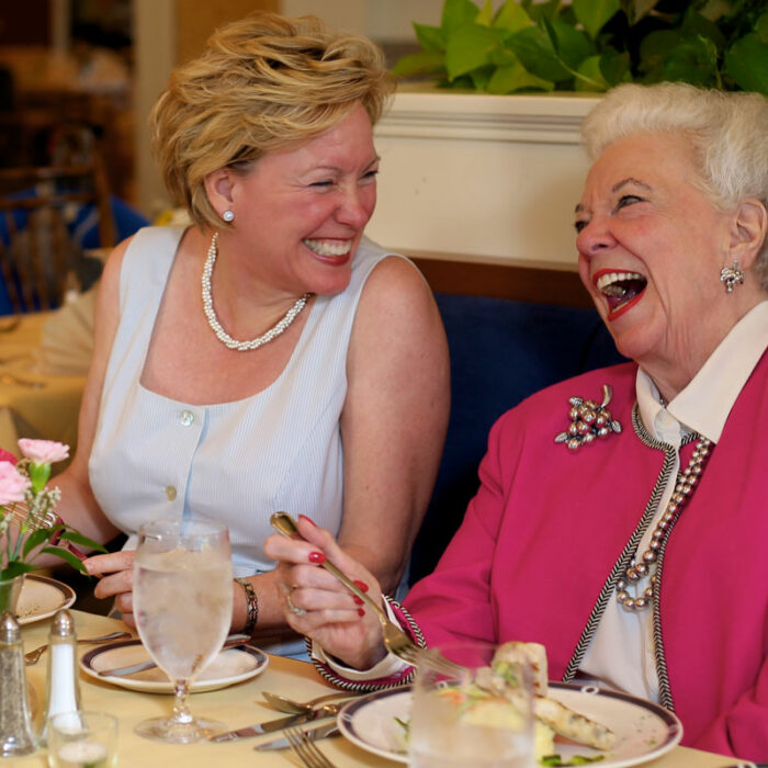 Two senior women laughing and eating together
