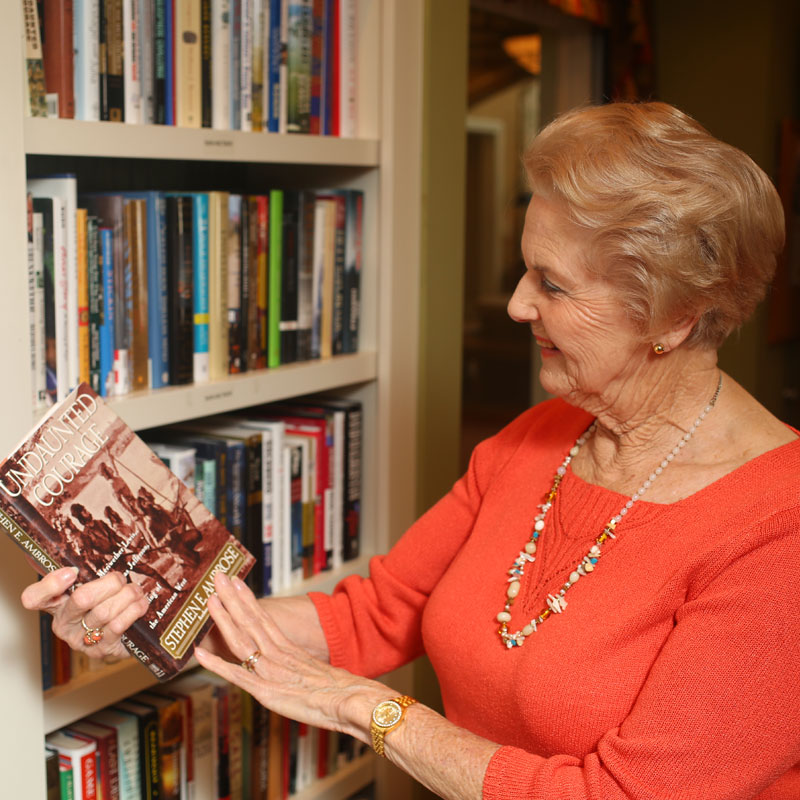 A senior woman pulls a book off the shelf in the library