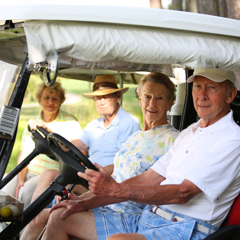 Two senior couples pose for his photos in their golf carts