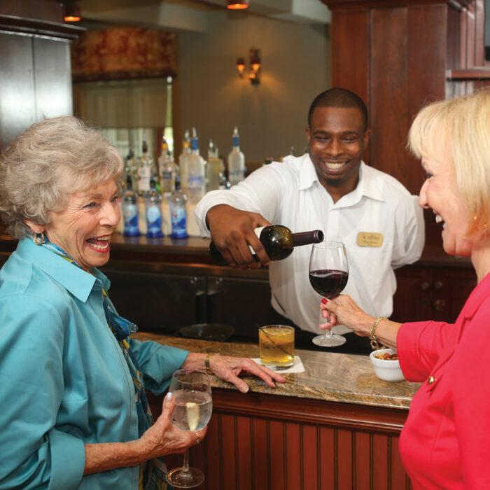 Senior women laughing and drinking wine