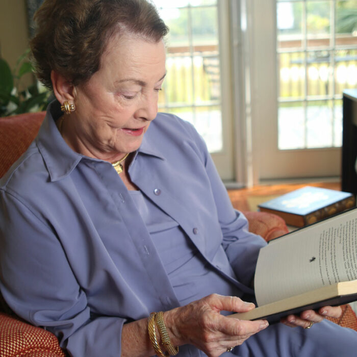 An elderly woman sits in an armchair and reads a book