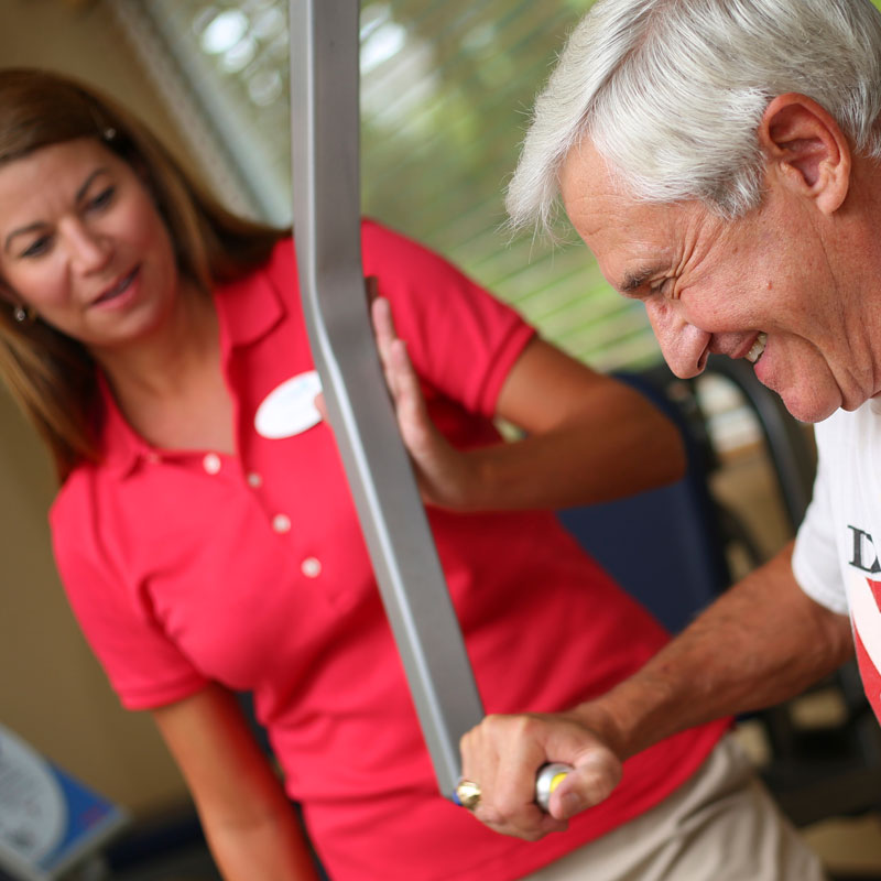 A trainer helps a senior man use workout machines