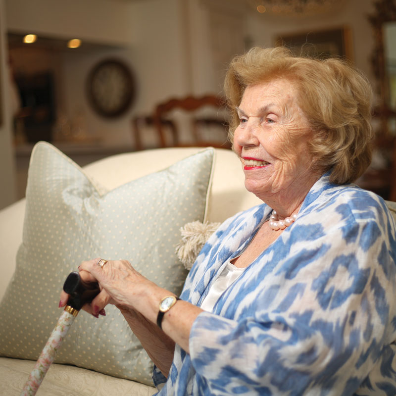 A senior woman sits on a couch and holds her decorative walking cane