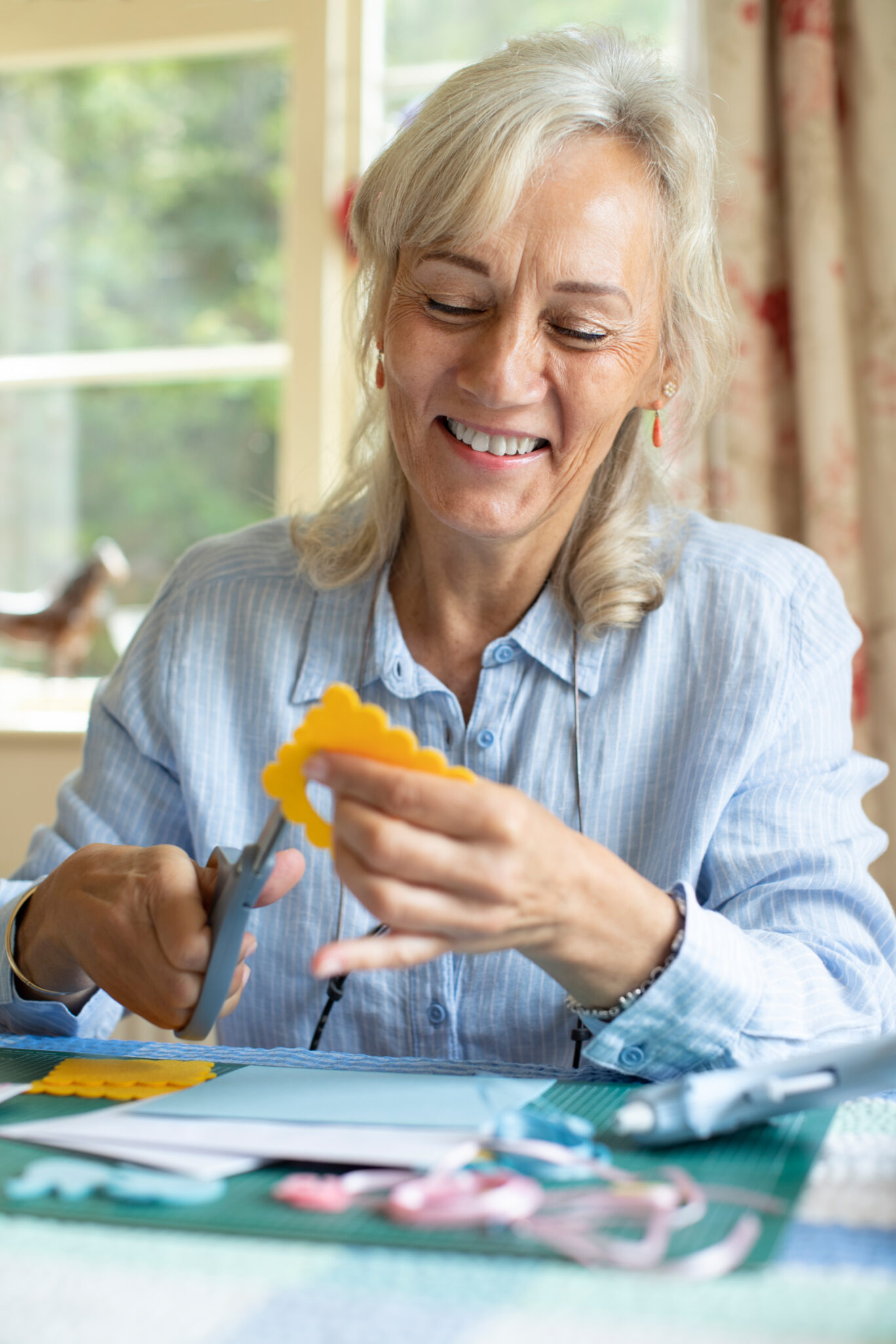 Senior woman cutting out paper