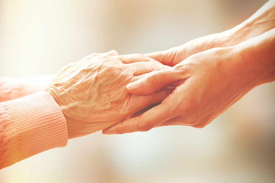 A close photo of an elderly pair of hand being held by a younger pair of hands