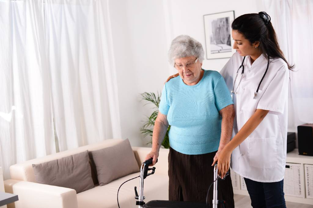 Nurse holding arms of assisted living resident with a walker