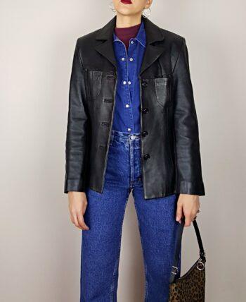 Veste en cuir. Couleur brun très foncé, presque noir. Col à revers. Poches poitrines. Coupe cintrée. Vintage des années 80.