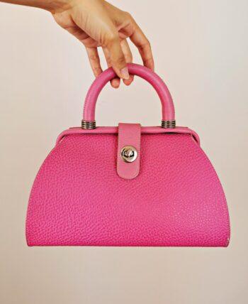 Sac rigide de la marque Paquetage, vintage des années 1980. Fabriqué en France. De couleur rose bubblegum. Détails en métal argenté. Porté main. Fermeture à loquet.