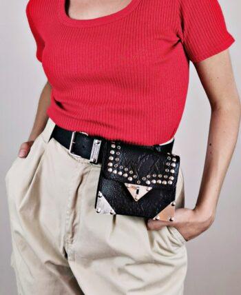 Sac ceinture en cuir noir embossé façon peau de serpent, vintage des années 1980. Fabriqué en France. Ornements clous et œillets en métal argenté. Coins de la pochette avec renforcement métal. Fermoir tourniquet.
