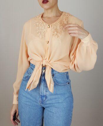 Chemisier transparent couleur abricot. Joli col dentelle et boutons façon perles. Vintage des années 80.