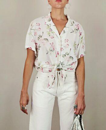 Chemisier manches courtes. Coupe ample, col à petit revers. Couleur blanc crème à motif fleuri. Coupe ample. Joli détails des boutons 3 par 3. Vintage des années 80.