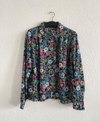 Chemise fluide fleurie à manches longues avec col arrondi, ceinture plissée élastique et boutons fantaisies.