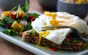 a healthy breakfast of eggs, vegetables, and avocado