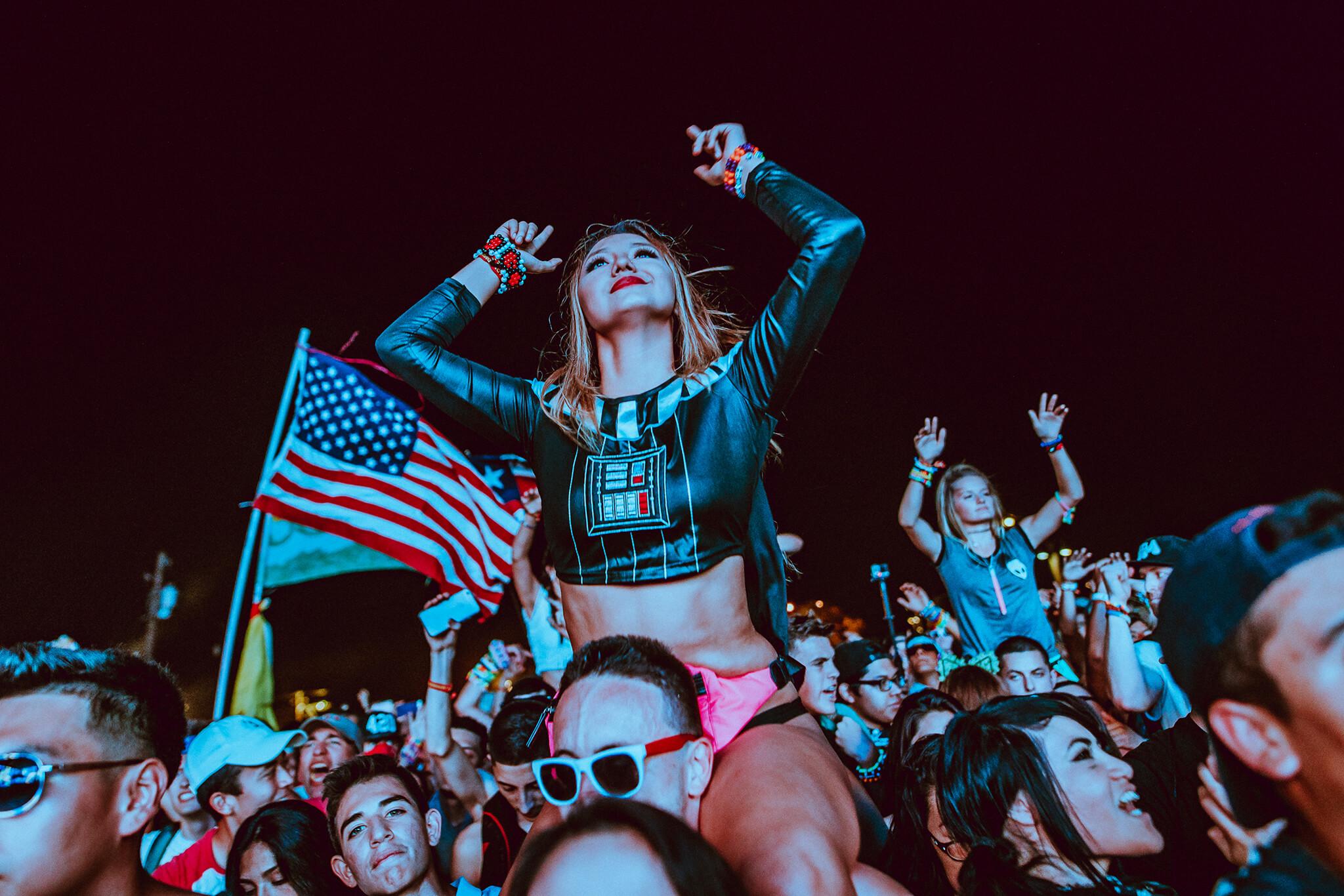 girl on guys shoulders in crowd