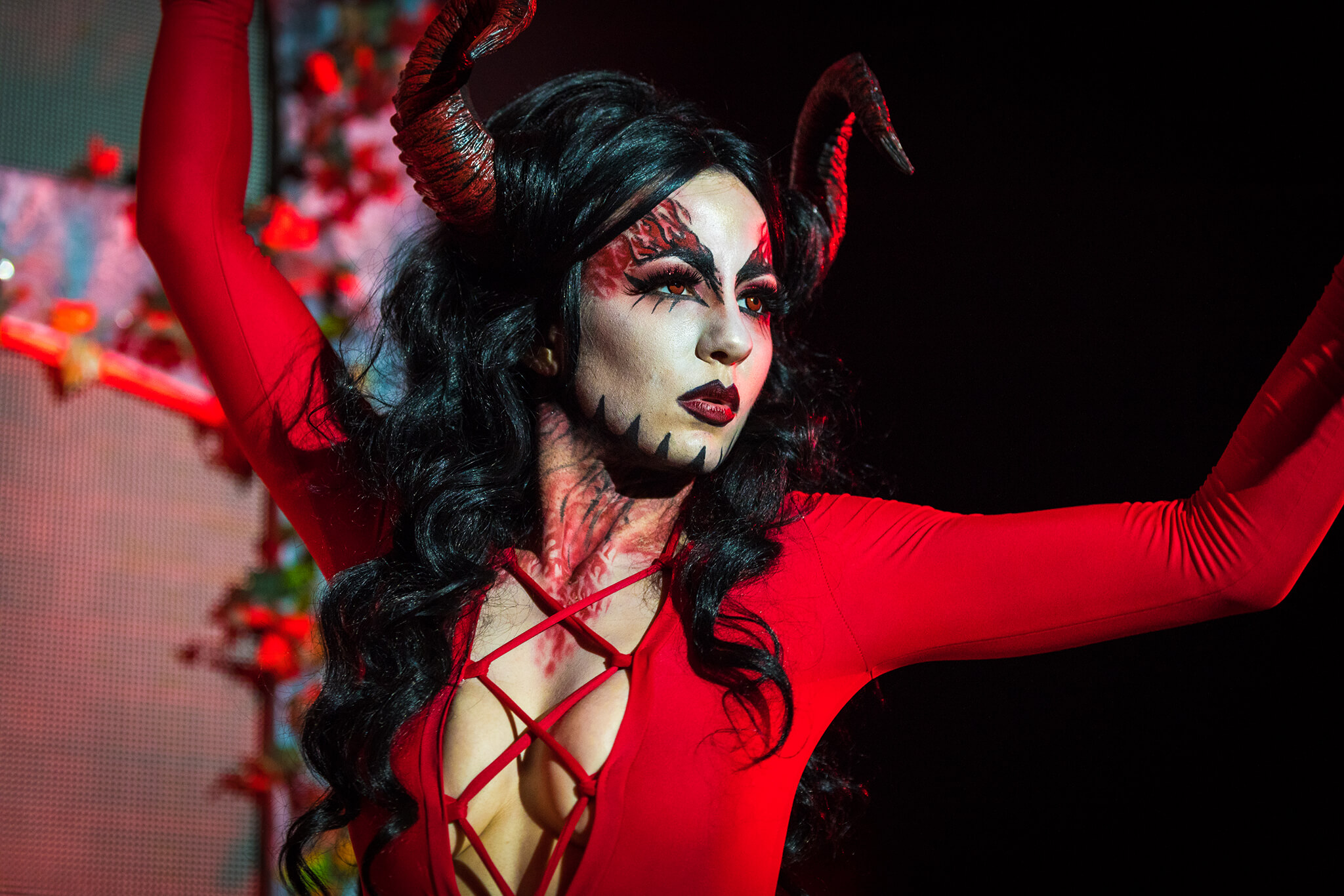 costumed devil performer looks far