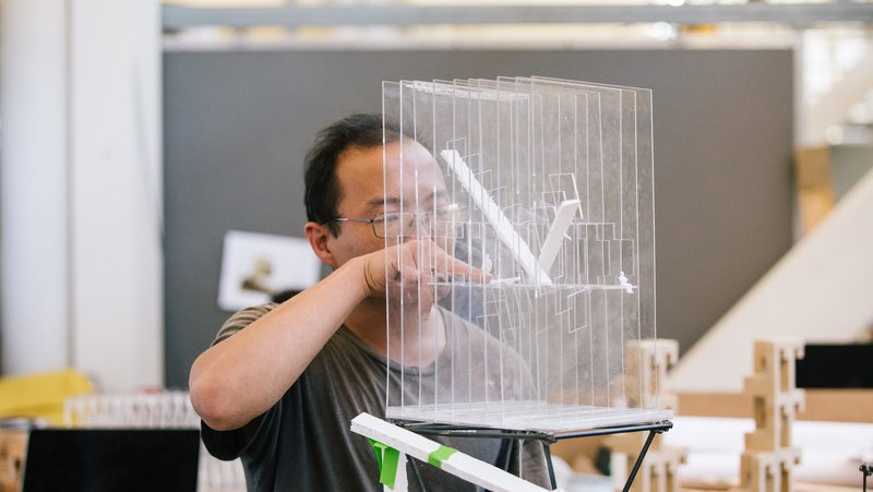 Architecture student working on their transparent model of a building_academics feature_MB