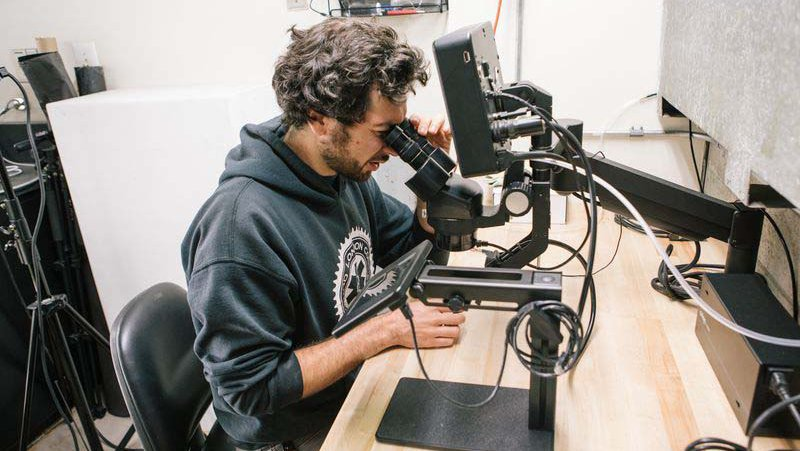Jewelry and Metal working student using microscope to examine and carve their jewelry