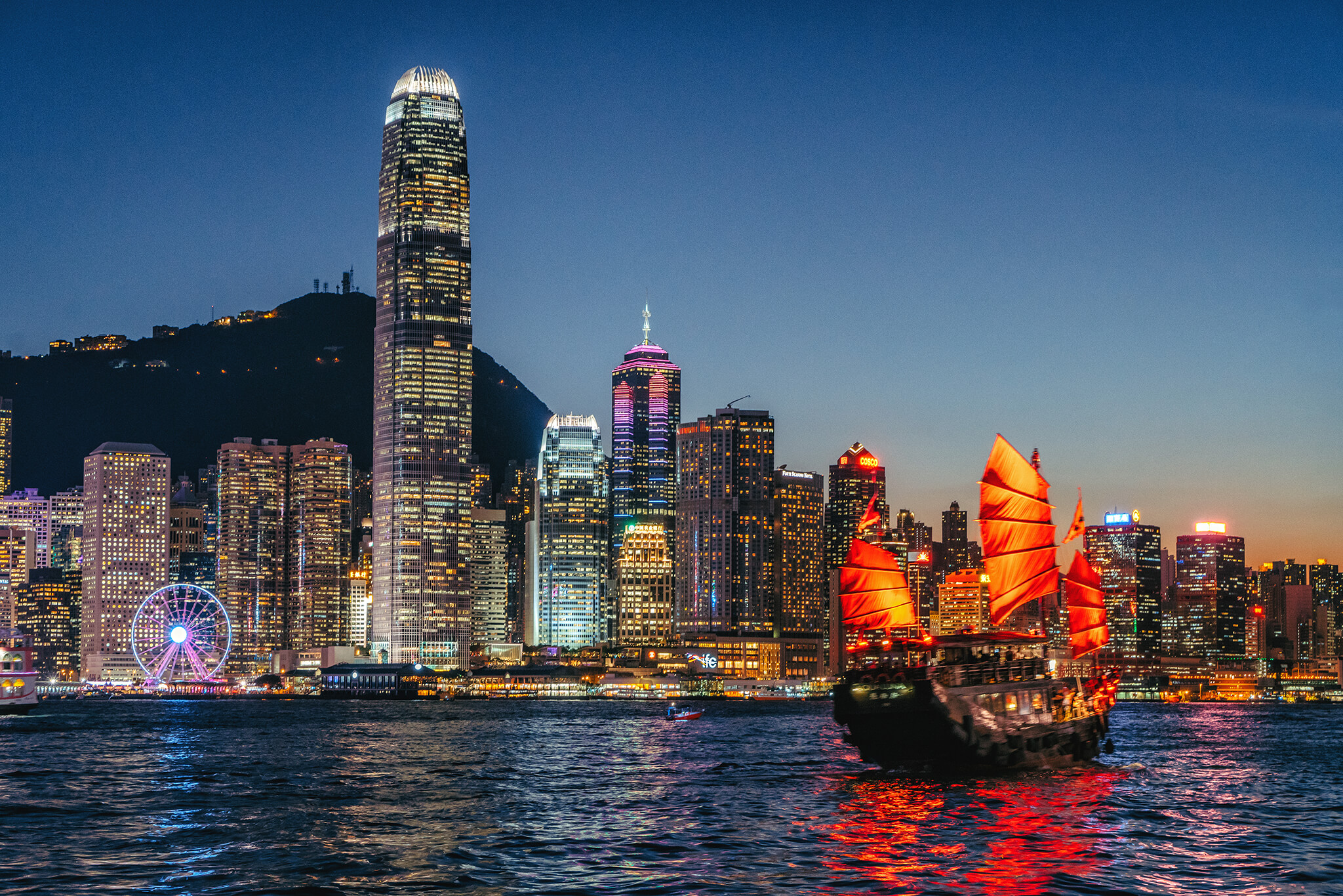 hong kong cityscape and junkboat at twilight