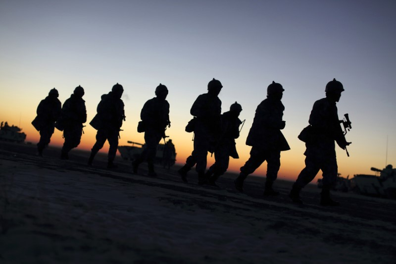 Soldiers of the People's Liberation Army Marine Corps march during a military drill as the sun rises at a military base in Taonan Jil