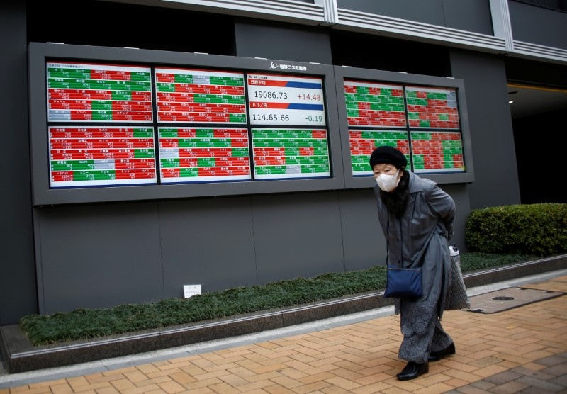A woman walks past electronic boards showing stock prices outside a brokerage in Tokyo Japan