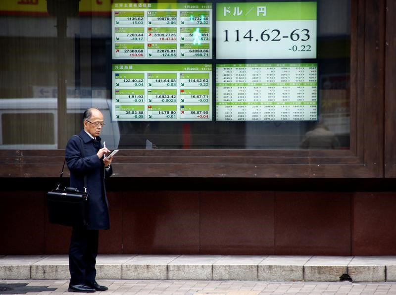 A man stands in front of electronic boards showing stock prices and exchange rate between Japanese Yen and U.S dollar outside a brokerage