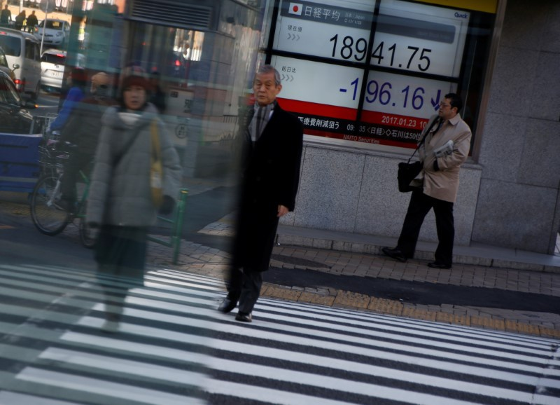 People walk past an electronic board showing stock prices outside a brokerage at a business district in Tokyo Japan
