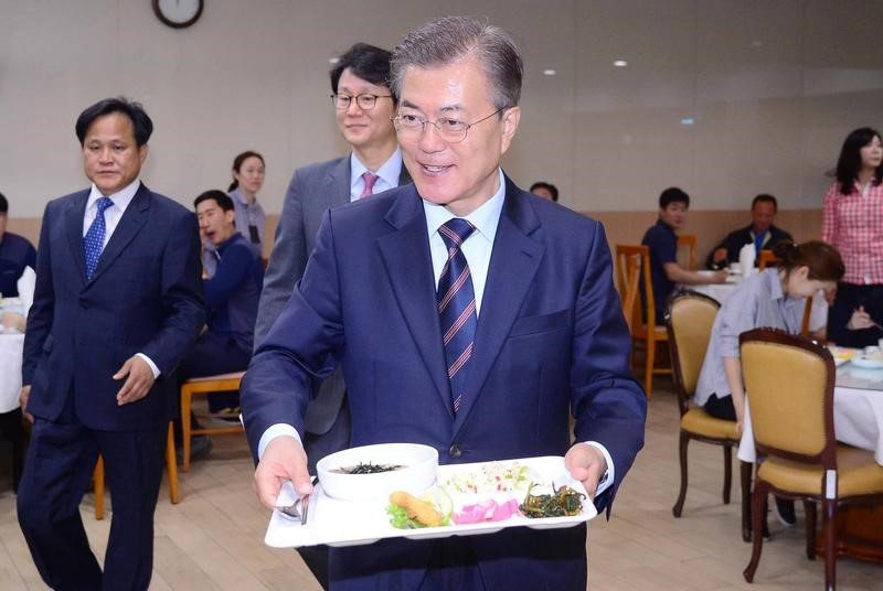 South Korean President Moon Jae-in carries a food tray as he has lunch with technical staff of the Presidential Blue House at an employee