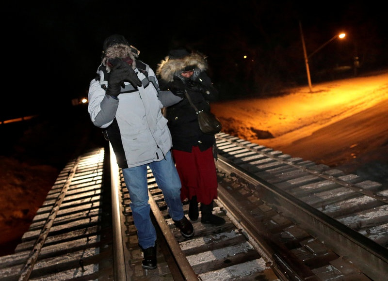 FILE PHOTO - Refugees walk along railway tracks from the United States to enter Canada at Emerson, Manitoba, Canada, on February 26, 2017. R