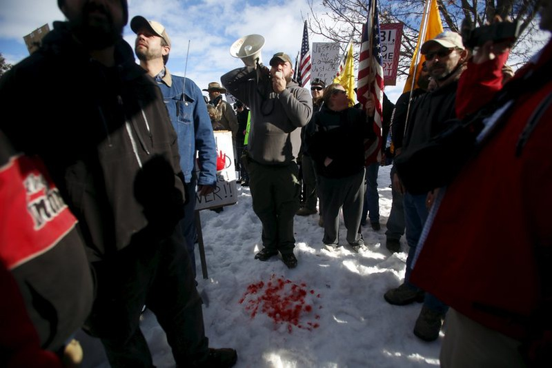 "Andrew Bedortha of the Pacific Patriots Network talks on a megaphone from behind red dye meant to symbolize the blood of Robert ""LaVoy"" Fini"