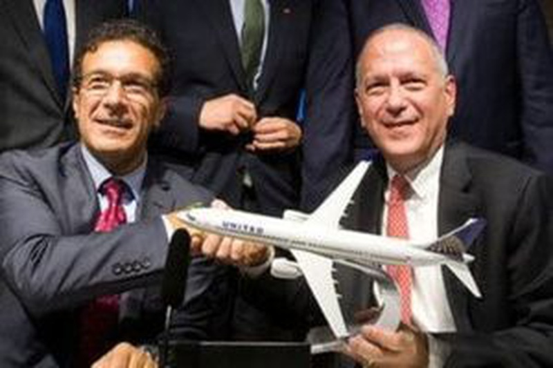 Vice President of Boeing Commercial Airplanes Ihssane Mounir shakes hands with United Airlines Senior Vice President of finance Gerry
