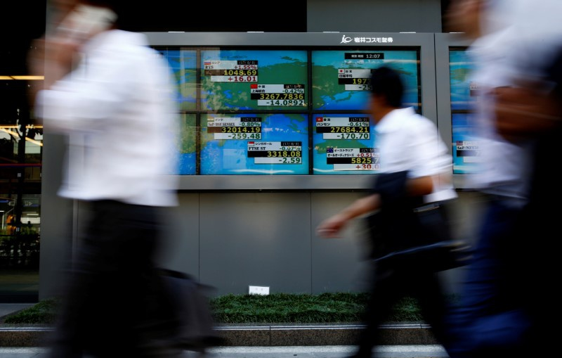 People walk past an electronic board showing Japan's Nikkei average outside a brokerage at a business district in Tokyo Japan