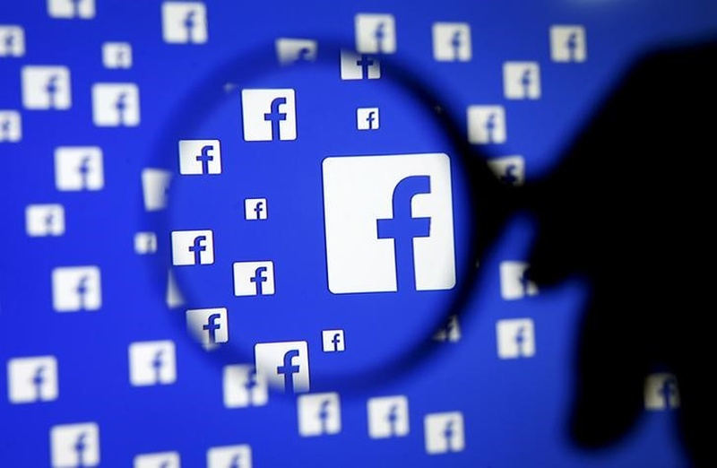 A man poses with a magnifier in front of a Facebook logo on display in this illustration taken in Sarajevo Bosnia and Herzegovina December