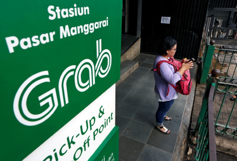 A woman uses her phone near a sign for the online ride-hailing service Grab at the Manggarai train station in Jakarta Indonesia
