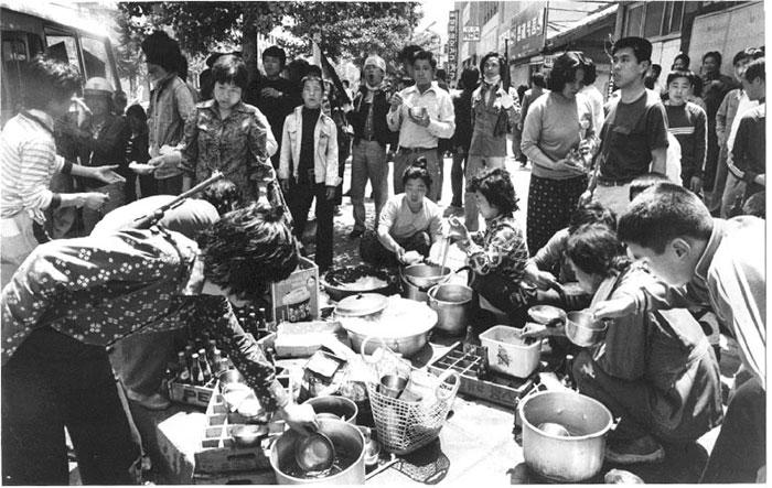 ▲ 5.18 민주화운동 기간 중 광주 거리, 시민들이 시위대를 위해 가져온 음식을 함께 먹고 있다.