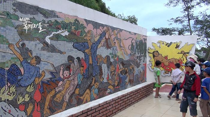 ▲ 따이한 제사가 열리는 고자이 마을에는 당시 학살 현장의 벽화가 설치되어 있다.
