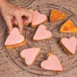 Biscotti accoppiati a forma di cuore con ghiaccia rosa