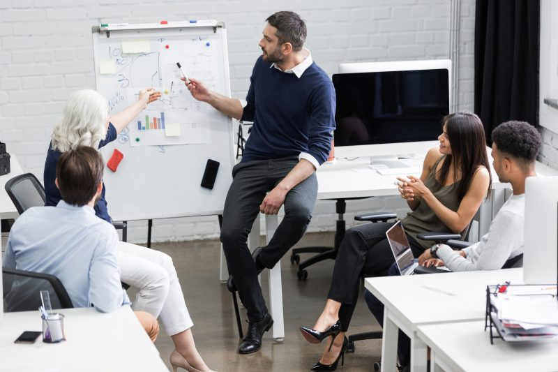 Creative people sitting at table in boardroom - Como ser um bom lider