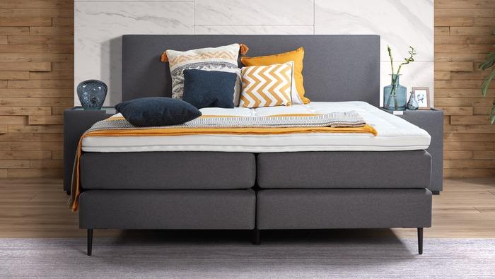 Modern boxspring bed in blauwgrijze stof met hoofdbord en nachttafels