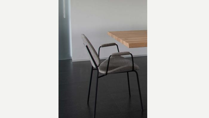 Grijze stoel in stof met armleuning op zwarte metalen poten
