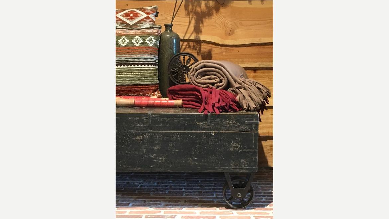 Zwarte houten kist op wielen als salontafel