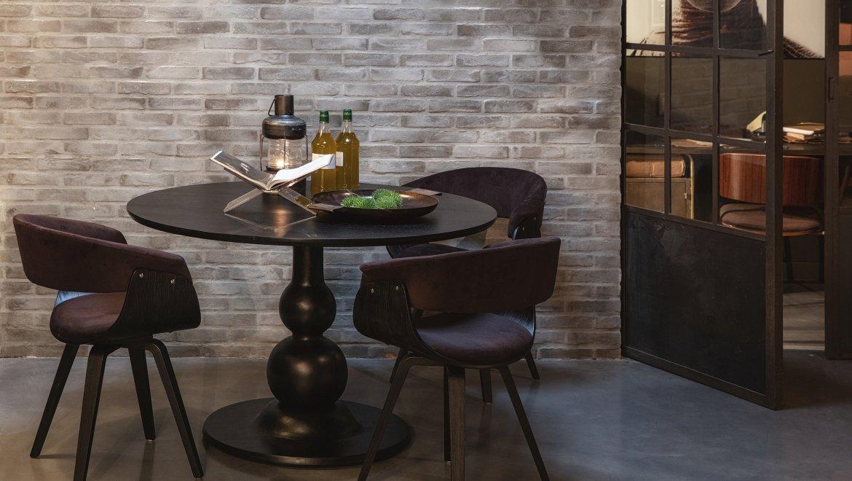 ronde zwarte tafel met gedraaide centrale poot op een platte voet