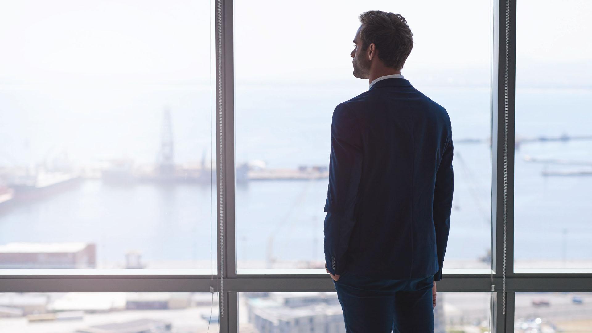 A imagem traz um vendedor olhando pela janela e refletindo sobre as suas vendas