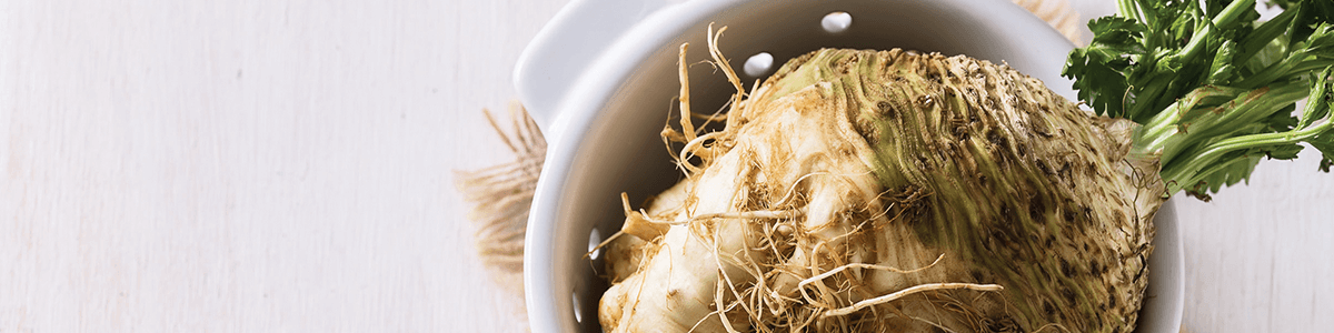 Image of celery root and stalk in a white bowl