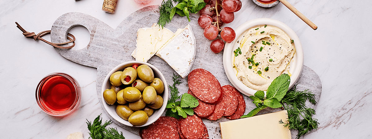 Image of a charcuterie platter with Goodfood cheese, meats, hummus, olives, grapes