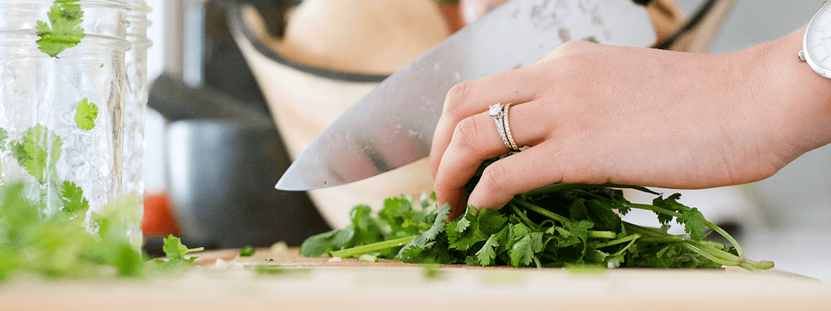 Image of person cutting herbs on a cutting board