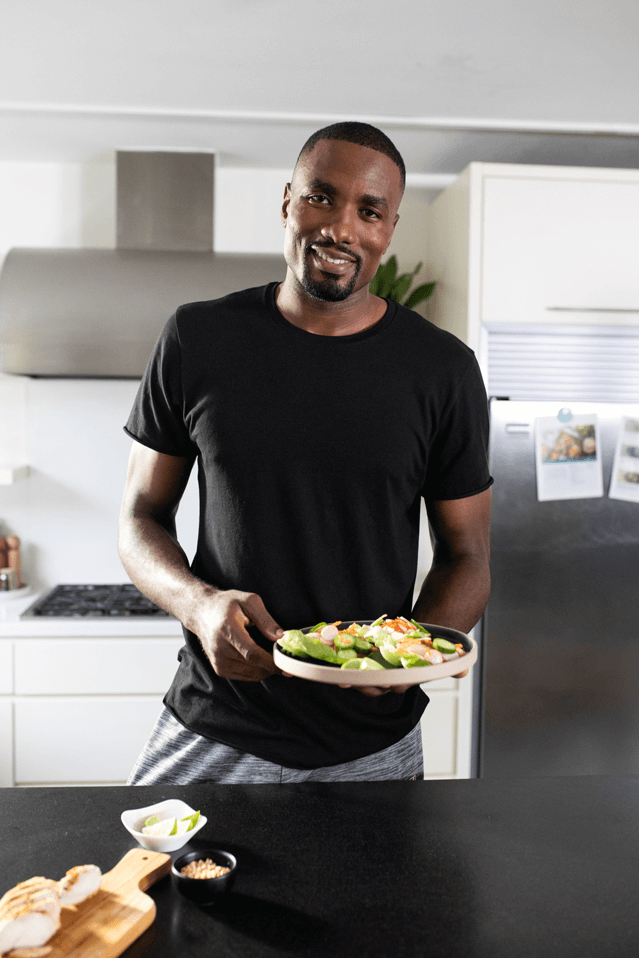 Serge Ibaka in a kitchen holding a plate of Goodfood